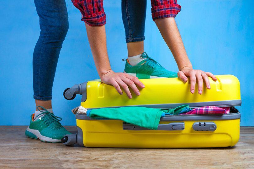 Żółta walizka pełna rzeczy - Jak się spakować na wyjazd