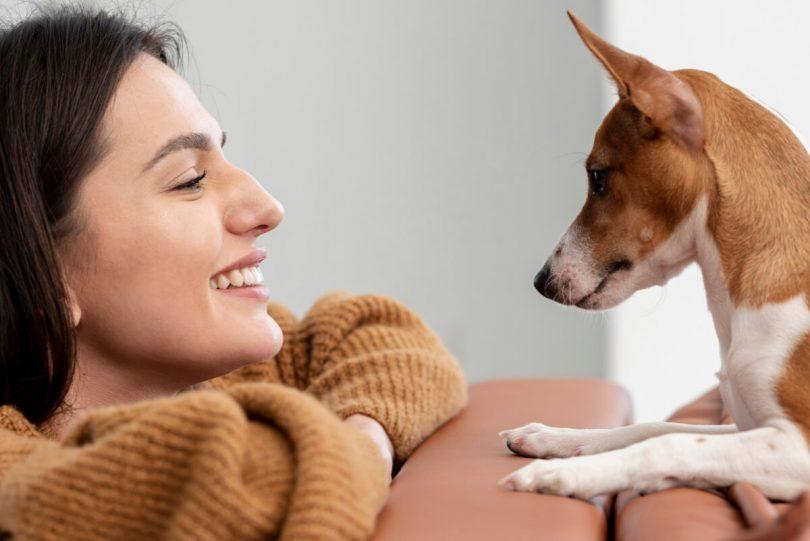 Uśmiechnięta kobieta i pies - Jaką rasę psa wybrać i na co zwrócić uwagę