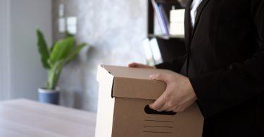 Zwolniony pracownik z pudełkiem - Utrata pracy - jak poradzić sobie z takim stresem